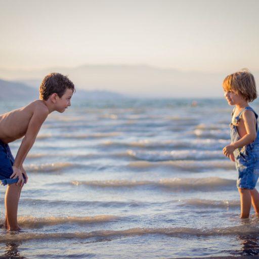 To barn ved en sjø som leker